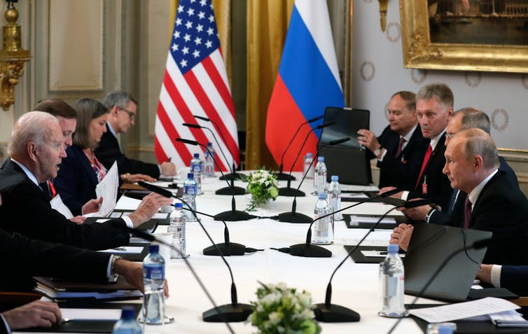 US President Joe Biden and Russian President Vladimir Putin face each other across the table during their meeting in Geneva, June 16 2021.