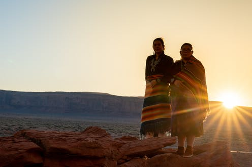 Two Navajo sisters dressed in traditional clothing standing in the desert with the sun behind them.
