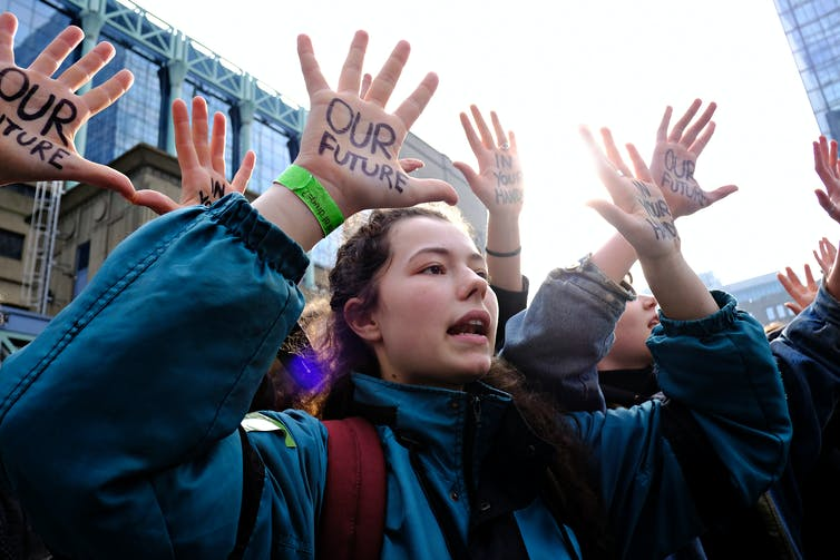 Students stand with their hands up, on their palms in sharpie reads 'OUR FUTURE'