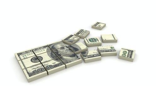Stack of $100 bills broken into pieces