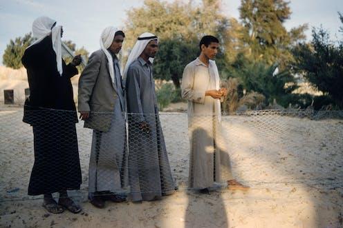 Quatre hommes debout en robes grises et beiges.