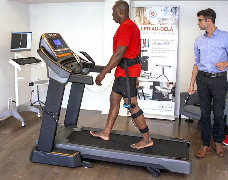 Bruny Surin marche sur un tapis roulant avec un harnais attaché à la jambe