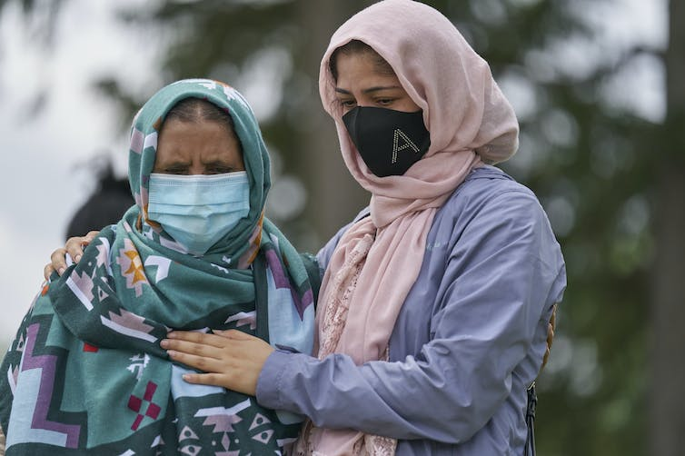 Two women wearing hijabs stand with their arms around each other.