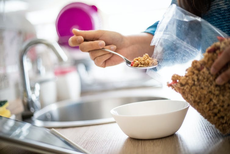 hand spoons cereal from a packet into bowl