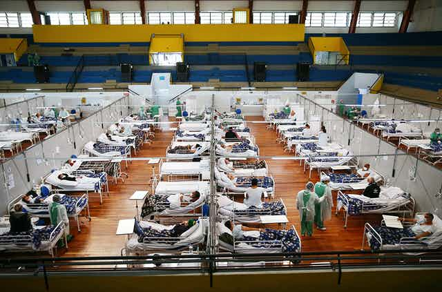 Aerial shot of dozens and dozens of beds with sick patients lined up in a gym