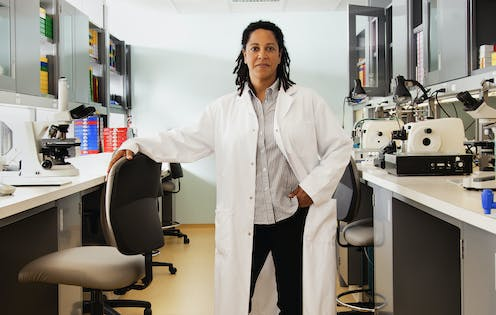 A woman in a white lab coat stands in the middle of a laboratory, her left hand in her pocket and her right hand on a chair