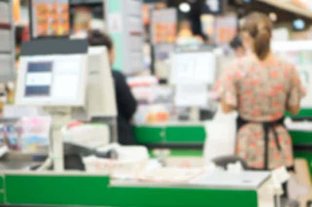 blurred supermarket checkout operator