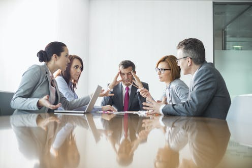 Man has head in hands as he chairs an acrimonious meeting