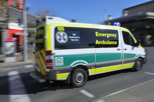 Ambulance rushing off to emergency along city street
