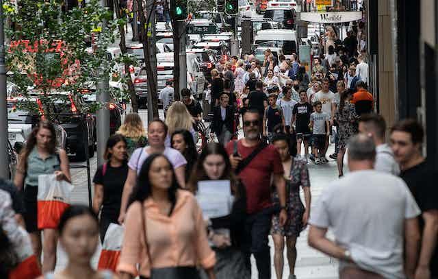 Crowd walking along street.