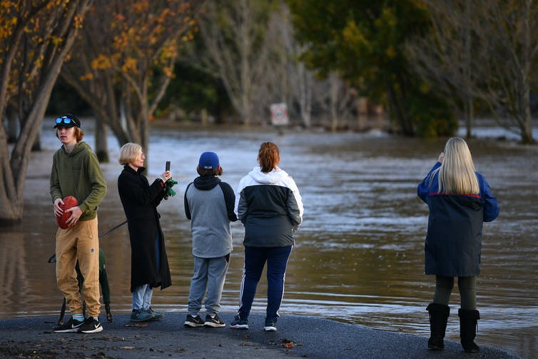 Five people looking at a flooded road