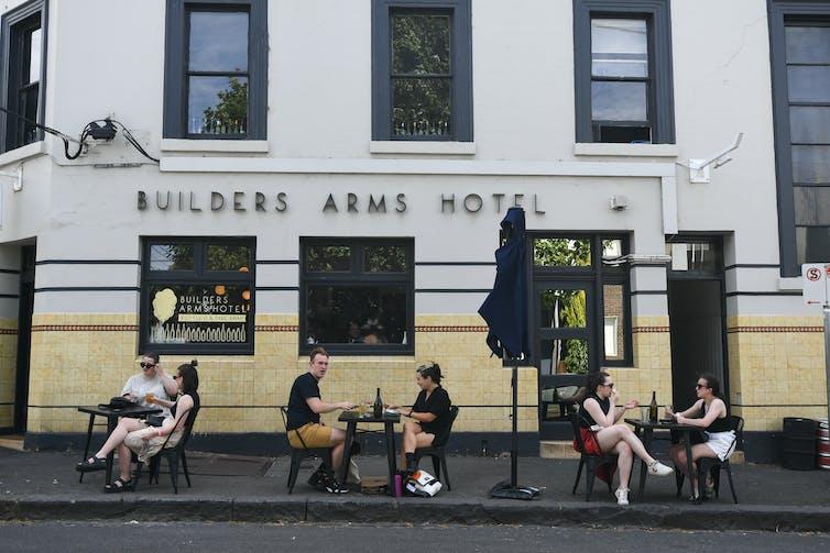 Patrons sit outside a pub.