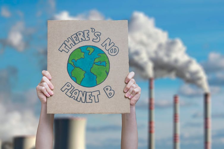 'There's no Planet B' sign with smoke stacks
