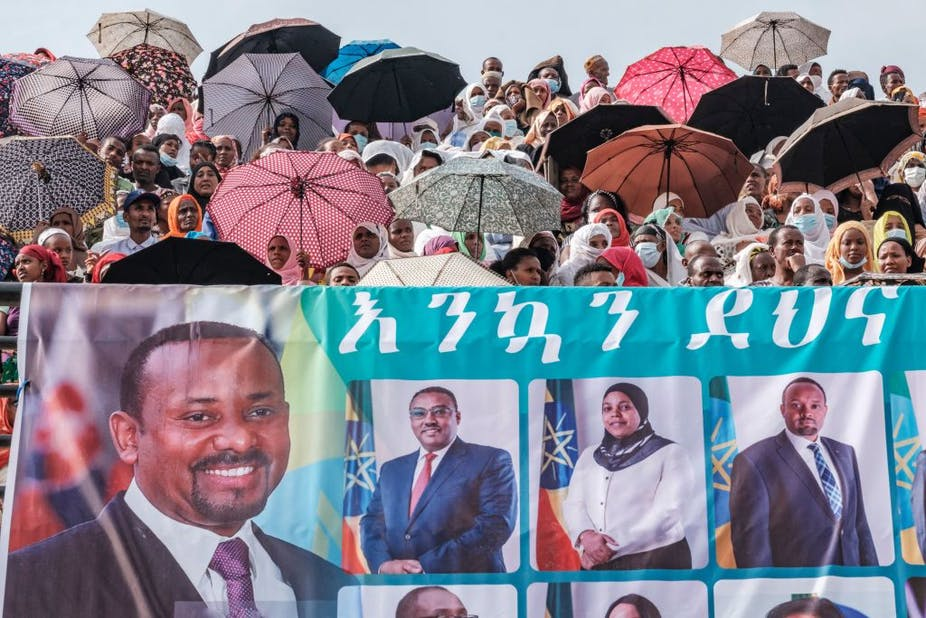 Crowd of people, some with umbrellas, and a large banner in the foreground depicting portraits of people