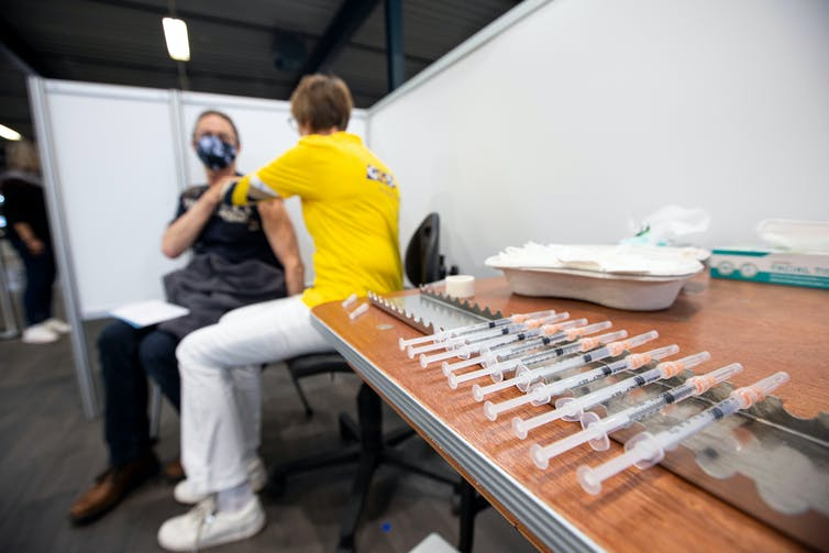 A man wearing facemask getting a COVID vaccine.