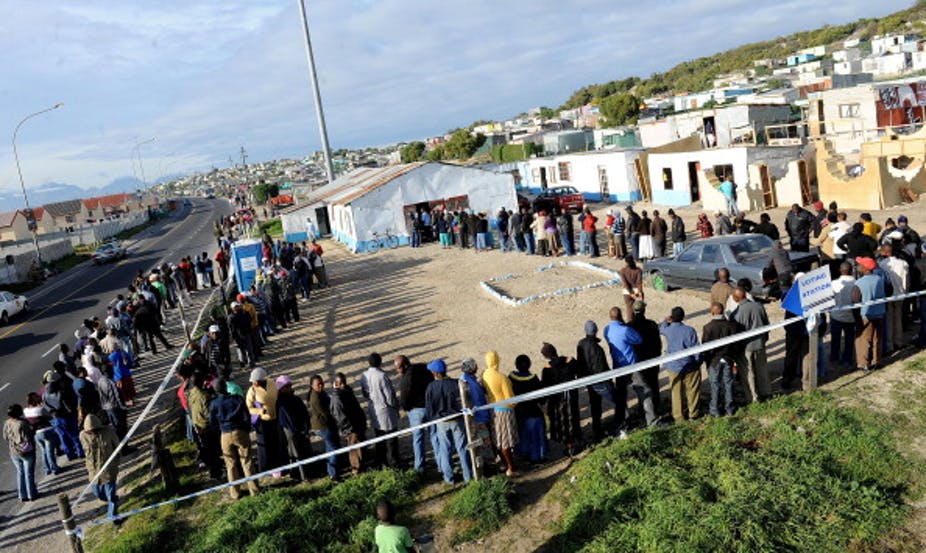 Men and women stand in a long, winding voting queue in an informal settlement in Cape Town, South Africa in a long, winding voting