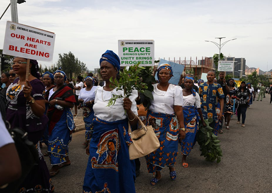 women marching peacefully on the streets with leaves and placards.