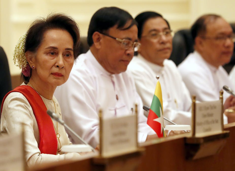 Myanmar leader Aung San Suu Kyi sitting at a conference with several colleagues form the National League for Democracy.