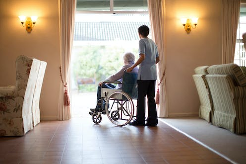 Elderly person in a wheelchair at a care home with a care home worker pushing the chair