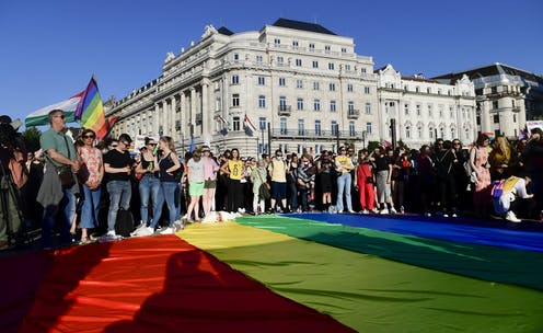 Protesters gather around a large Pride flag in front of the parliament building in Budapest