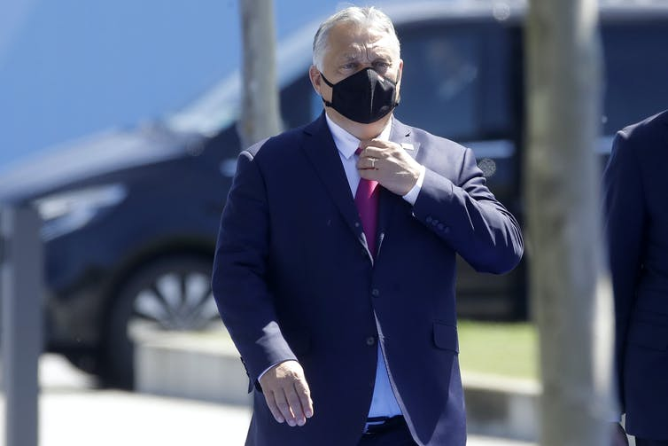 Viktor Orban, wearing a face mask, arrives at a recent NATO conference
