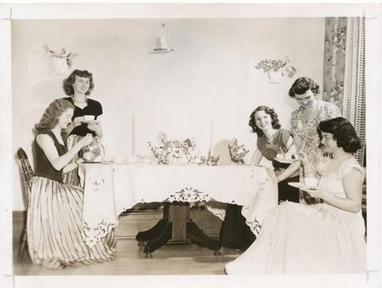 Women sit around a table having afternoon tea.