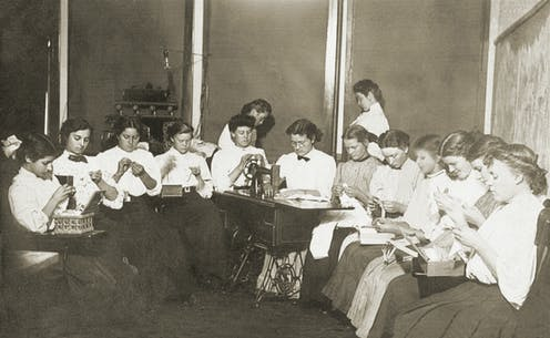 An archive photo of women sitting in a circle doing embroidery.