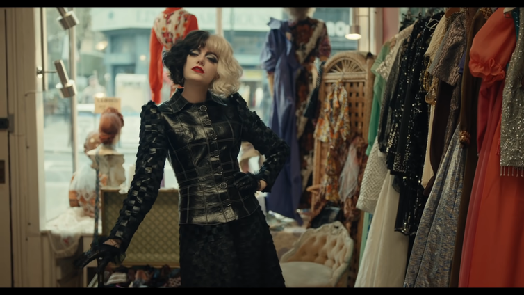 Emma Stone dressed as Cruella de Vil wearing black and white wig and black leather outfit in a shop