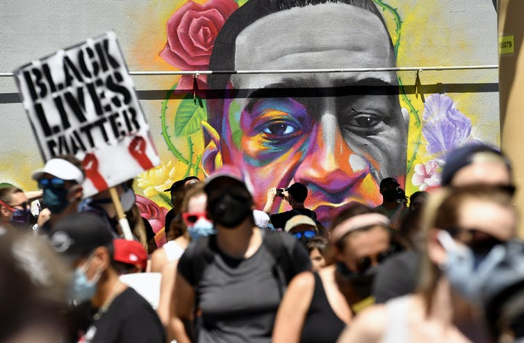 Marchers walk by a mural of George Floyd.