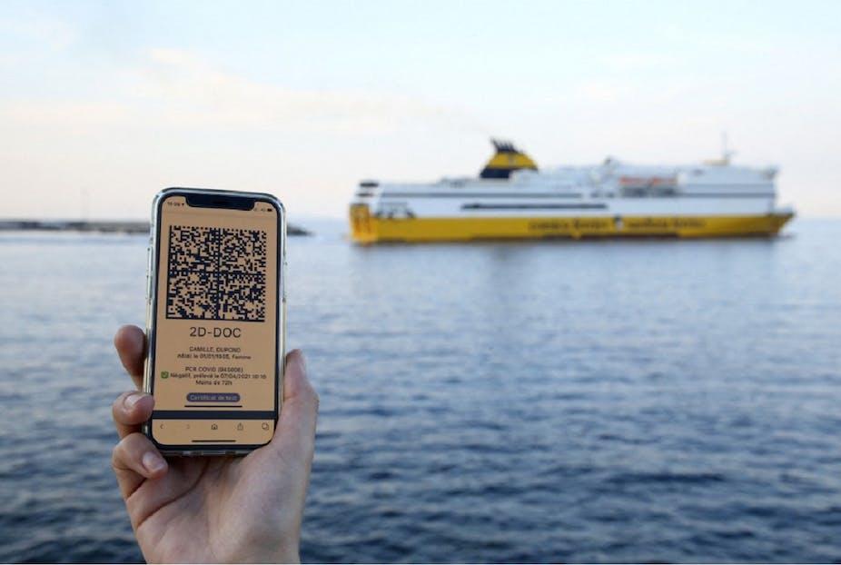 Une femme montre le QR code de son test PCR, devant un bateau Corsica Ferries au départ de Bastia, le 9 juin 2021.