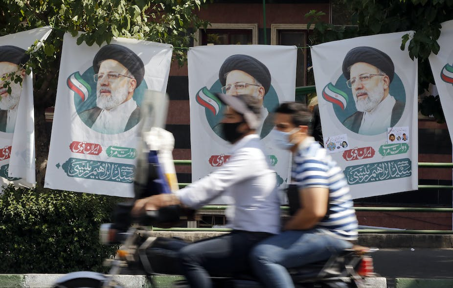Two Iranian men on a motorcycle ride past election flags for conservative candidate Ebrahim Raisi, Tehran, June 2021.