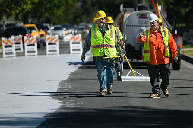 Workers spread light-colored coating on a roadway..