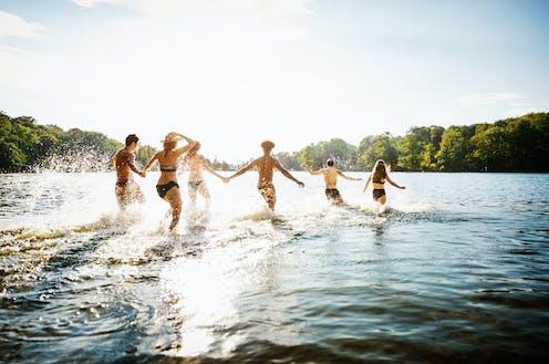 Groupe de personnes pataugeant dans un lac par une journée ensoleillée.
