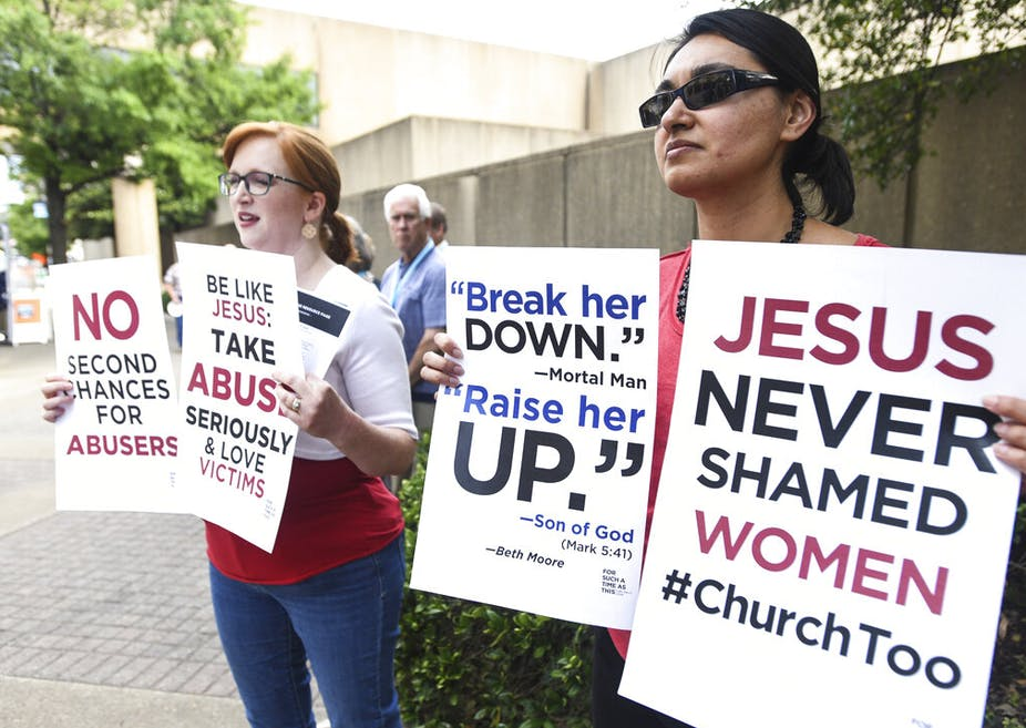 Two young women holding signs with slogans demanding action on church leaders' abuse of women and an end to shaming women victims of sexual abuse, outside a Southern Baptist Convention meeting in 2019.