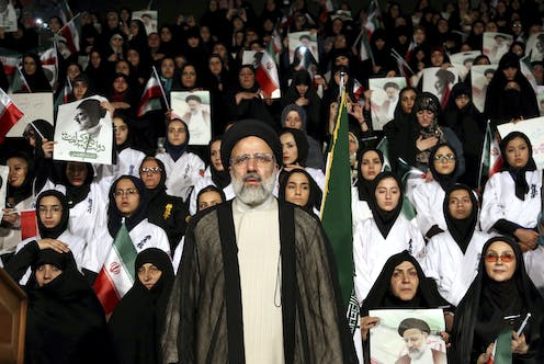 Ebrahim Raisi stands at a rally as supporters hold Iranian flags and pictures of him behind him