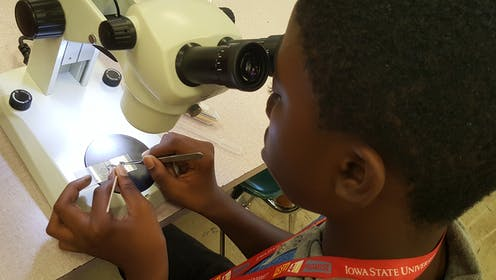 A young Black boy dissects a mosquito under a microscope.