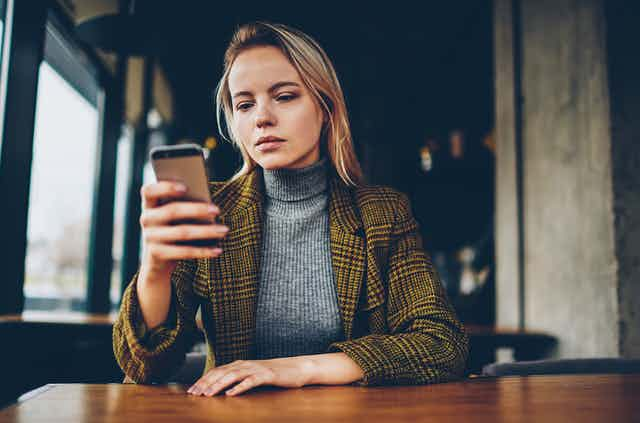 A young woman looks at her smartphone.