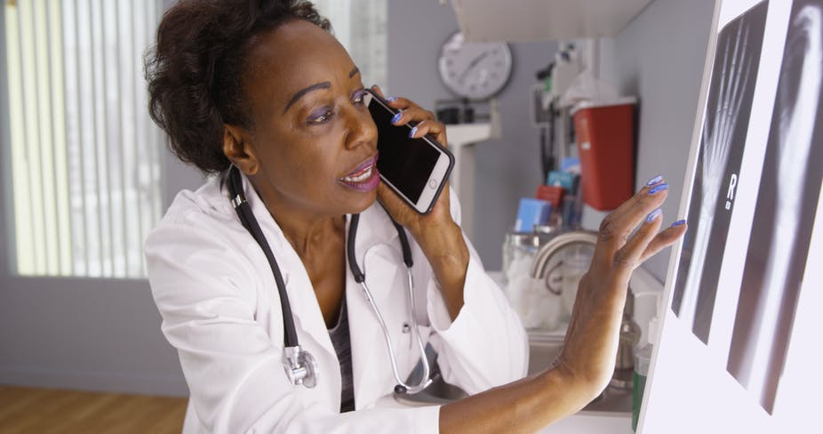 African female doctor communicating on phone with colleague while assessing x-ray images.
