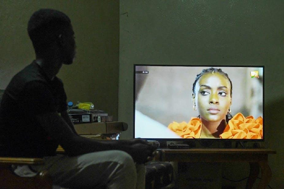 Un enfant regarde une série sénégalaise à la télévision