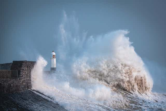 A lighthouse is buffeted by large waves during a storm.