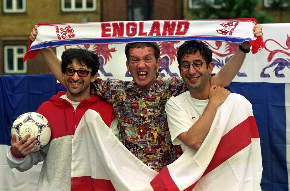 Three men holding the English flag, a football and an England scarf.