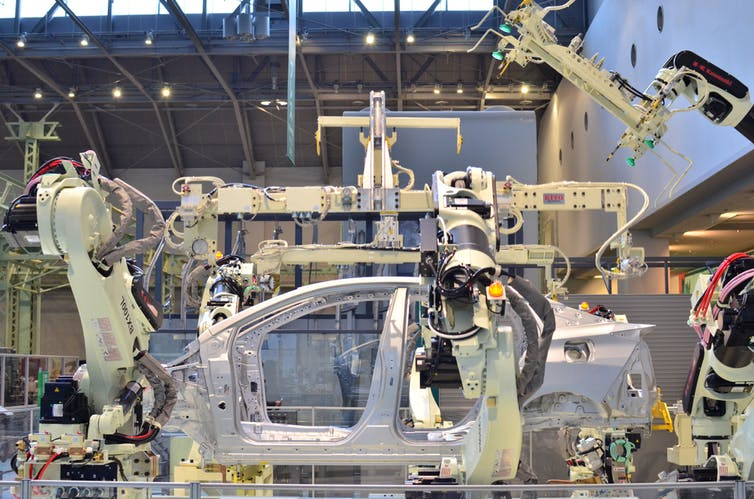 Robotic arms in factory assemble a car body shell.