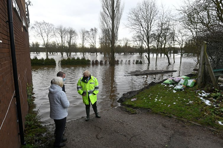 Boris Johnson talks with locals at the side of a flooded area.