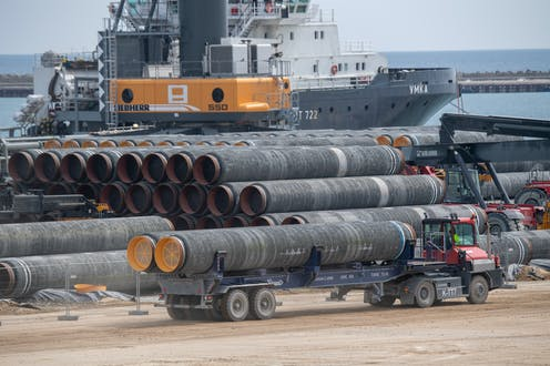 A truck drives two large pipes for the Nord Stream 2 Baltic Sea gas pipeline past several rows of similar pipes. In the background is a large ship and a crane to load the pipes.