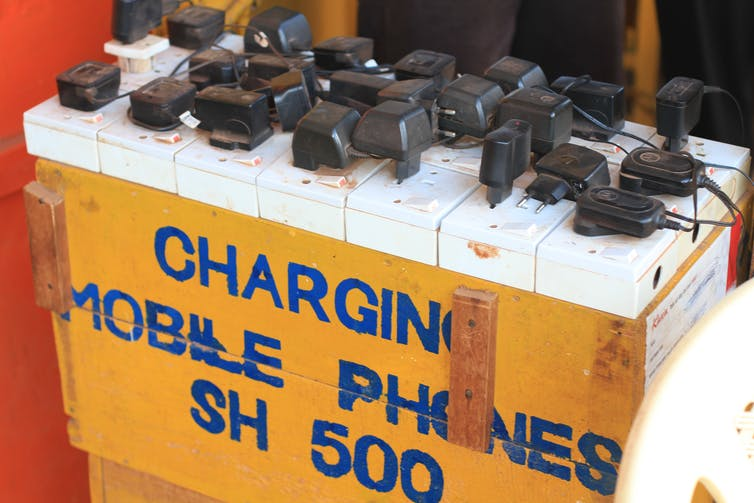 Plugs are plugged into a box marked 'CHARGING MOBILE PHONES SH 500'