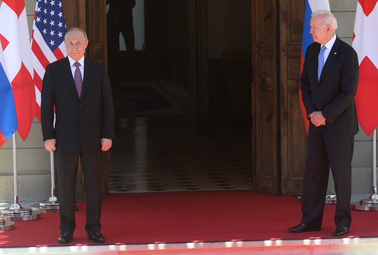 Vladimir Putin (left) and Joe Biden (right) stand in front of a door. Putin is facing the camera with a neutral expression. Biden is turned slightly to the left to look at Putin.