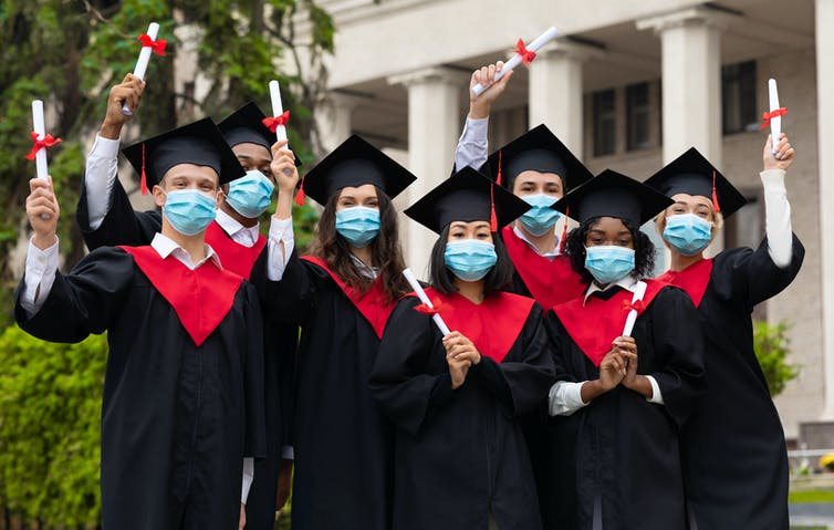 A group of graduates standing with diplomas wearing face masks.