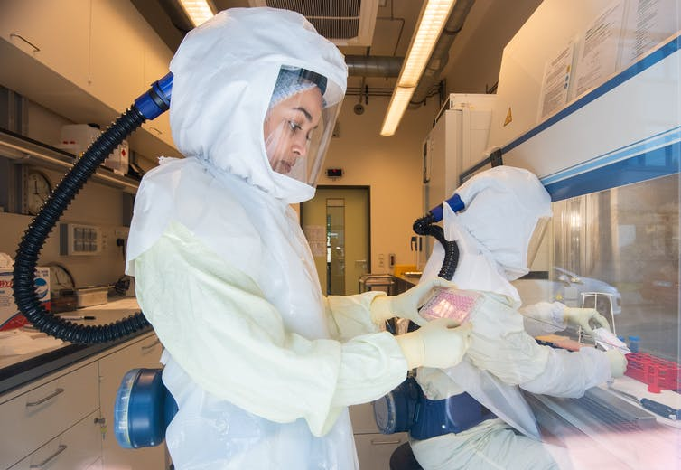 Two scientists in a COVID-19 research laboratory, wearing fully enclosed white protective suits with clear face screens and independent air supplies.