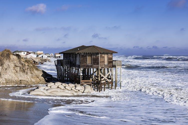 Una casa azotada por la tormenta sobre pilotes en Nags Head se asienta sobre el agua con sacos de arena debajo.