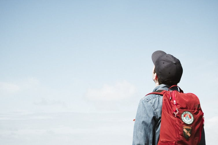 Back of a young person in backpack looking at the sky.